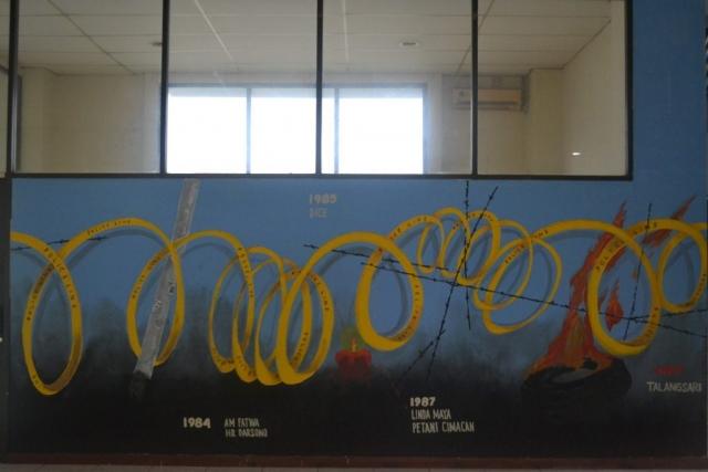 Mural ini terletak pada lantai satu gedung LBH Jakarta-YLBHI. Pada mural ini, simbol police-line, kawat berduri, dan kobaran asap dihadirkan dalam bentuk gulungan mirip kawat panjang seakan-akan kita berada dalam area demonstrasi yang besar dan penuh perjuangan.