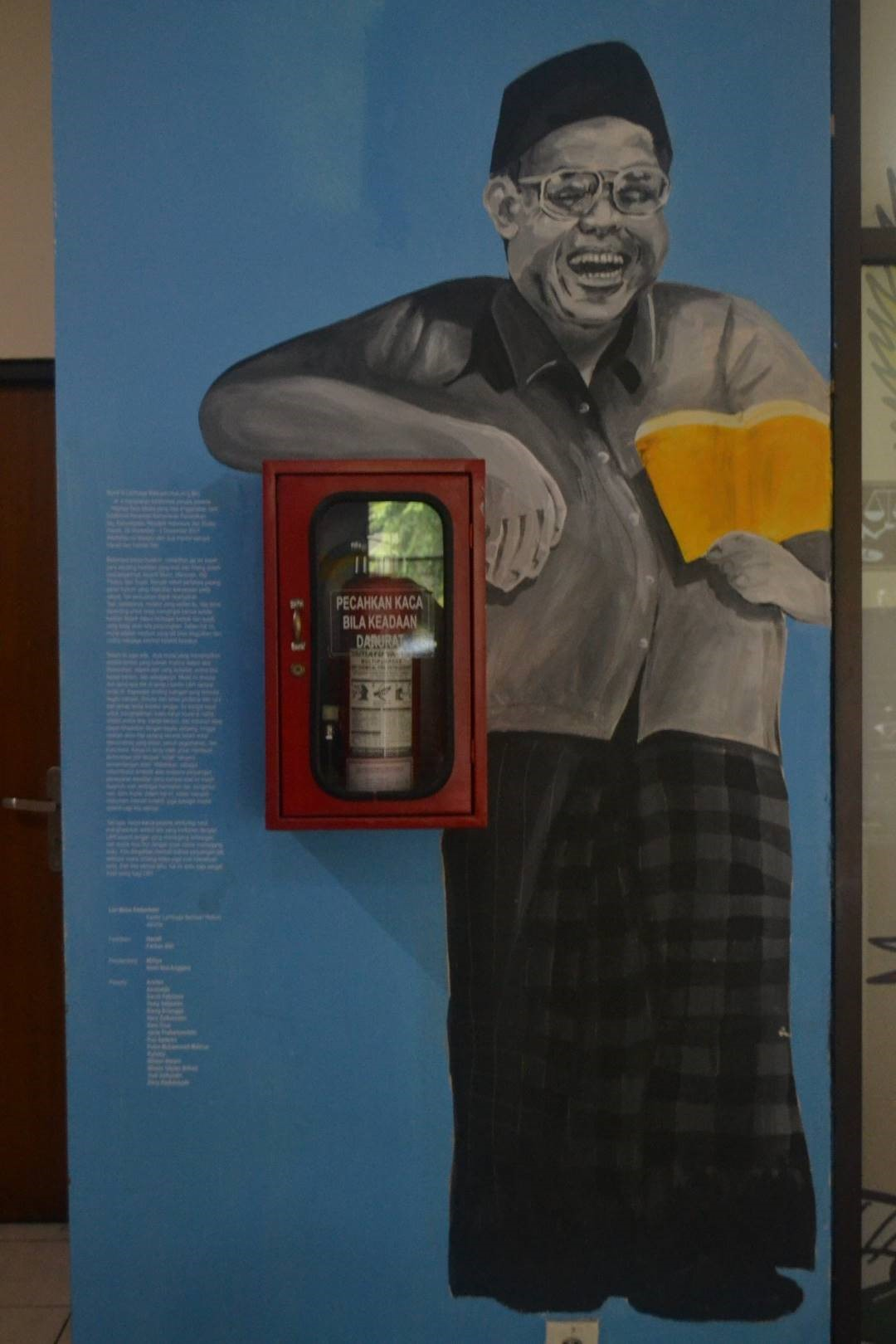 Di depan ruang konsultasi LBH Jakarta terdapat mural Gus Dur dengan pose santai memegang buku. Dalam mural ini kita diingatkan bahwa perjuangan tak hanya sekedar suara yang lantang, tetapi juga soal intelektualisme. Di sebelah mural Gus Dur terdapat penjelasan tentang arti mural di gedung Kantor Lembaga Bantuan Hukum serta nama-nama orang yang membantu menyukseskan pembuatan mural ini.