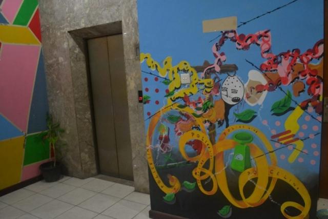 """Tak jauh dari mural Gus Dur, tepatnya di depan lift lantai 1 terdapat mural yang """"instagram-able"""" dengan komponen warna dan gambar yang menarik. Hal ini menunjukkan bahwa di setiap perjuangan pasti terdapat keceriaan."""