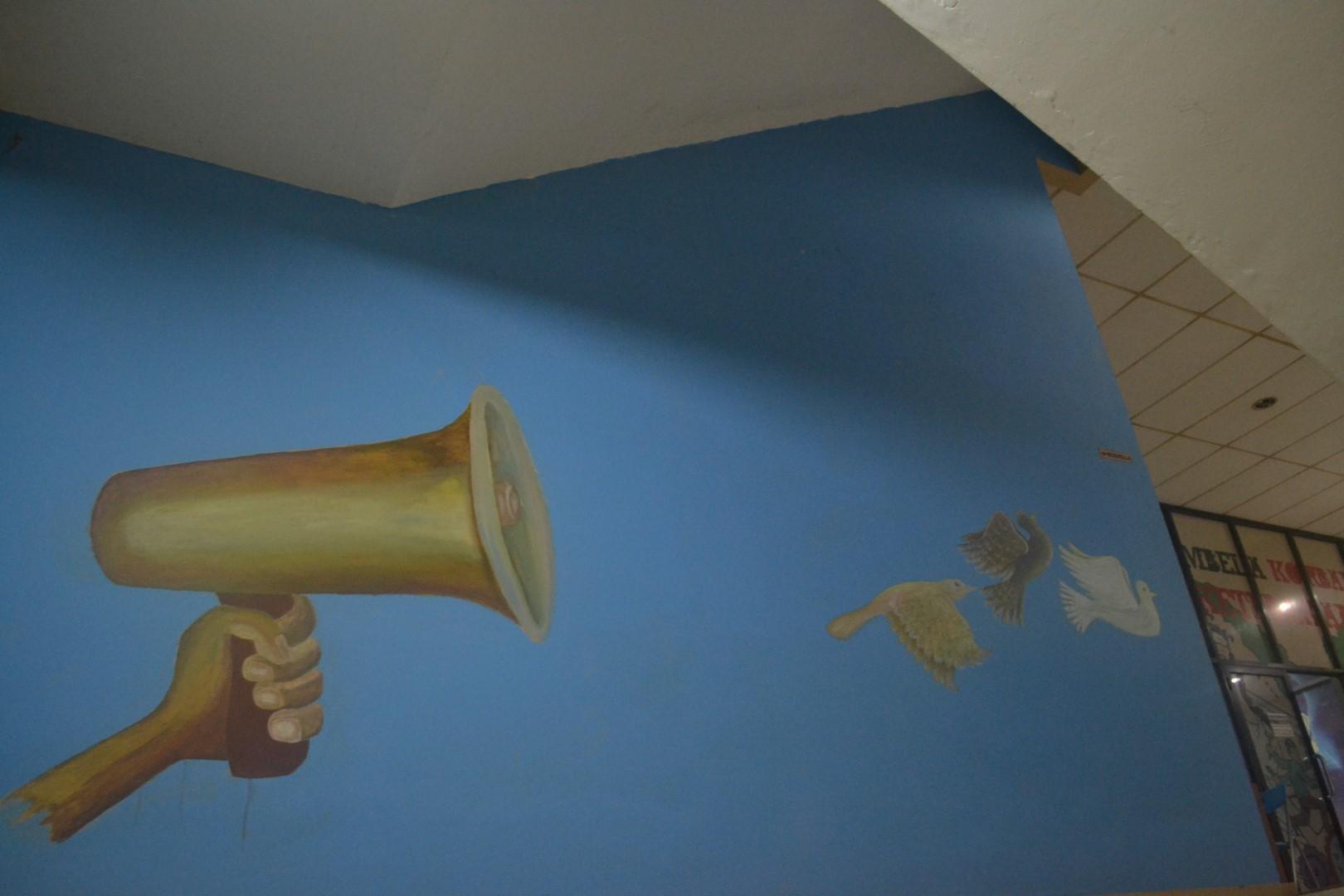 Tak jauh dari mural Marsinah, Wiji Thukul, dan Suyat terdapat mural toa yang dipegang lalu mengeluarkan 3 ekor burung. Mural ini melambangkan bahwa perjuangan dapat terbang dan dibawa kemana saja.